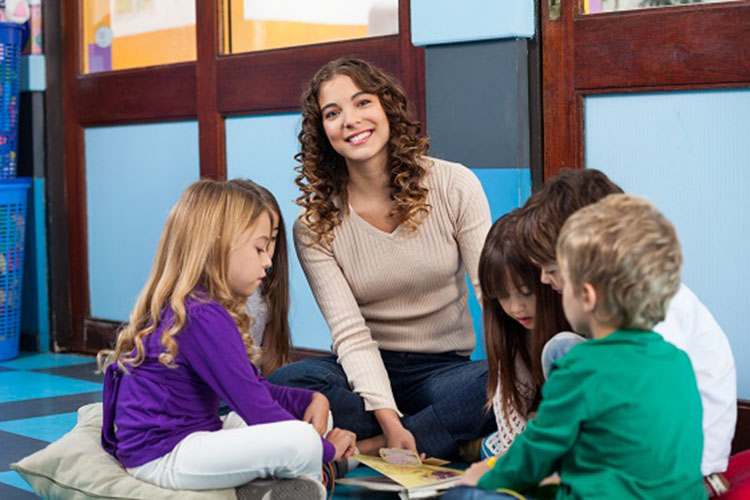 Portrait of young teacher with children reading book while sitting on floor in classroom